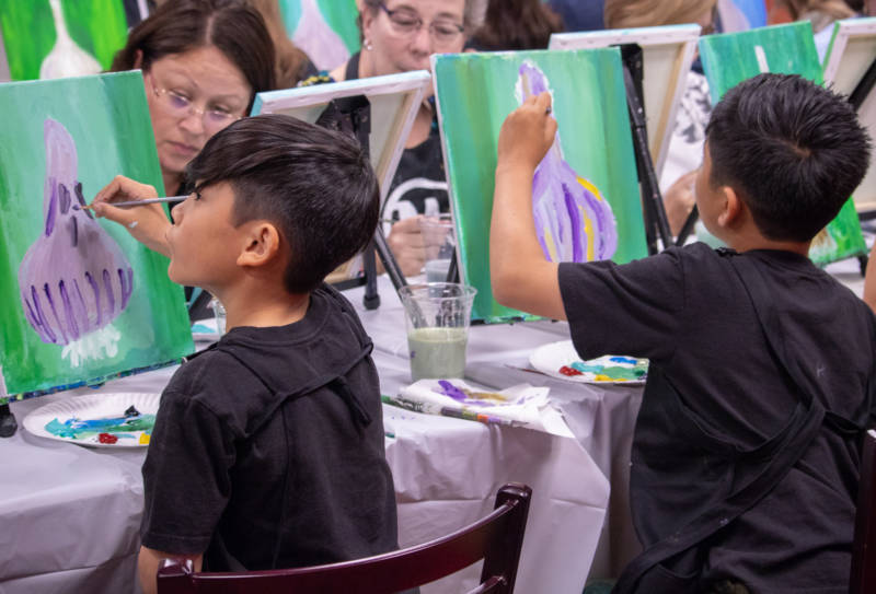 Brothers Colin Diep, 8, and Ethan, 10, try their hand at painting the garlic bulb, an important symbol of Gilroy, at a fundraiser for survivors of the shooting on Aug. 5, 2019, in Gilroy.
