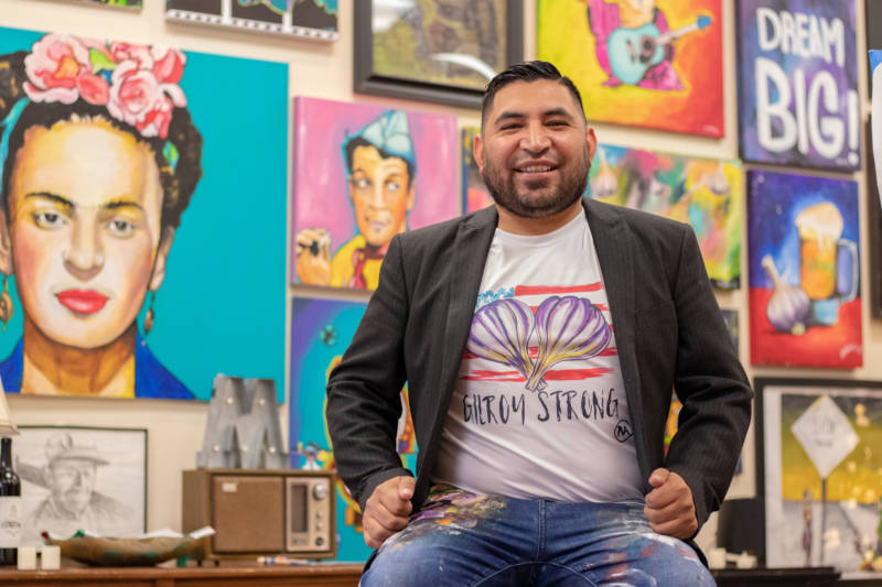 """Ignacio """"Nacho"""" Moya in his Gilroy studio on Aug. 5, 2019. Moya said his Mexican heritage, the community of Gilroy, where he grew up, and world events influence his artwork. He is wearing a T-shirt bearing artwork he created for a banner at a vigil the day after the July 28 shooting at the Garlic Festival."""