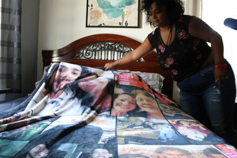 Alicia Saddler lays out a blanket with photos of her brother, Angel Ramos, and their mother.