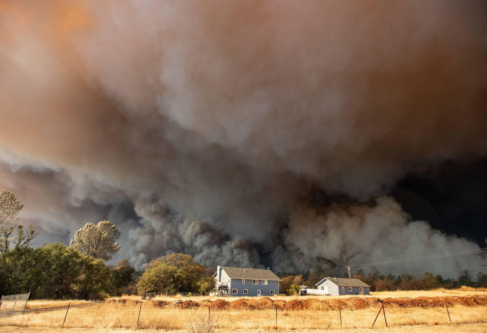 A home is overshadowed by towering smoke plumes as the Camp fire races through town in Paradise, California on November 08, 2018.  Josh Edelson/AFP/Getty Images