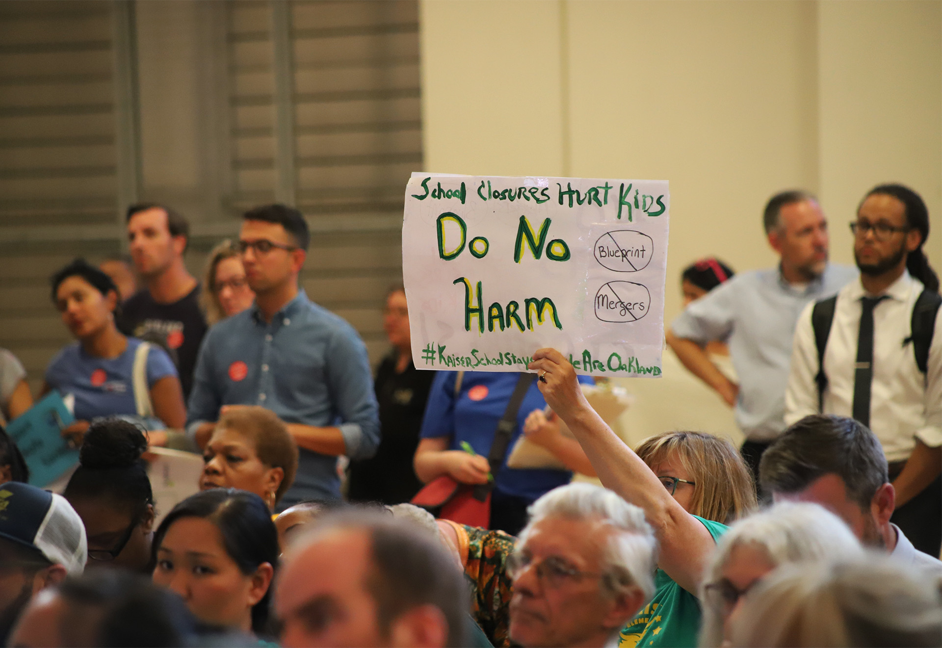 """An attendee at an Aug. 28, 2019 OUSD board meeting holds a sign reading """"Do Not Harm"""" in opposition to the district's plan to merge Henry J. Kaiser Jr. Elementary with another school."""