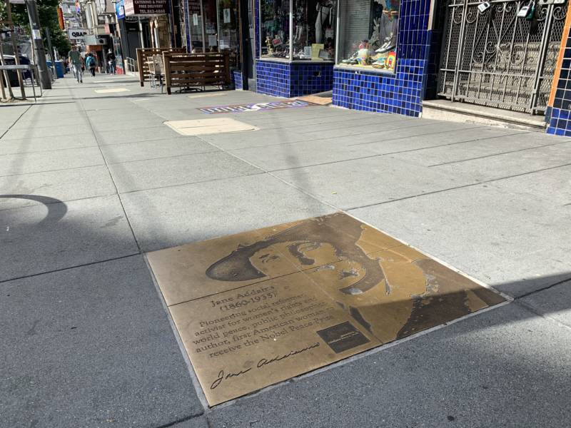 A sidewalk plaque on Castro Street in San Francisco honors Jane Addams, a pioneering social worker who won the Nobel Peace Prize in 1931.