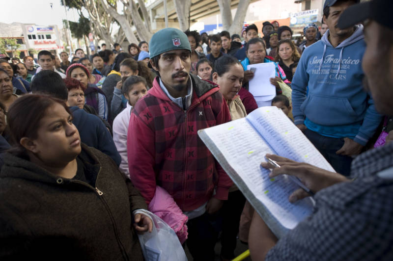 People listen as a man calls out the names on a waiting list whose turn it is to walk to the U.S. border crossing in Tijuana where they will then ask for asylum.