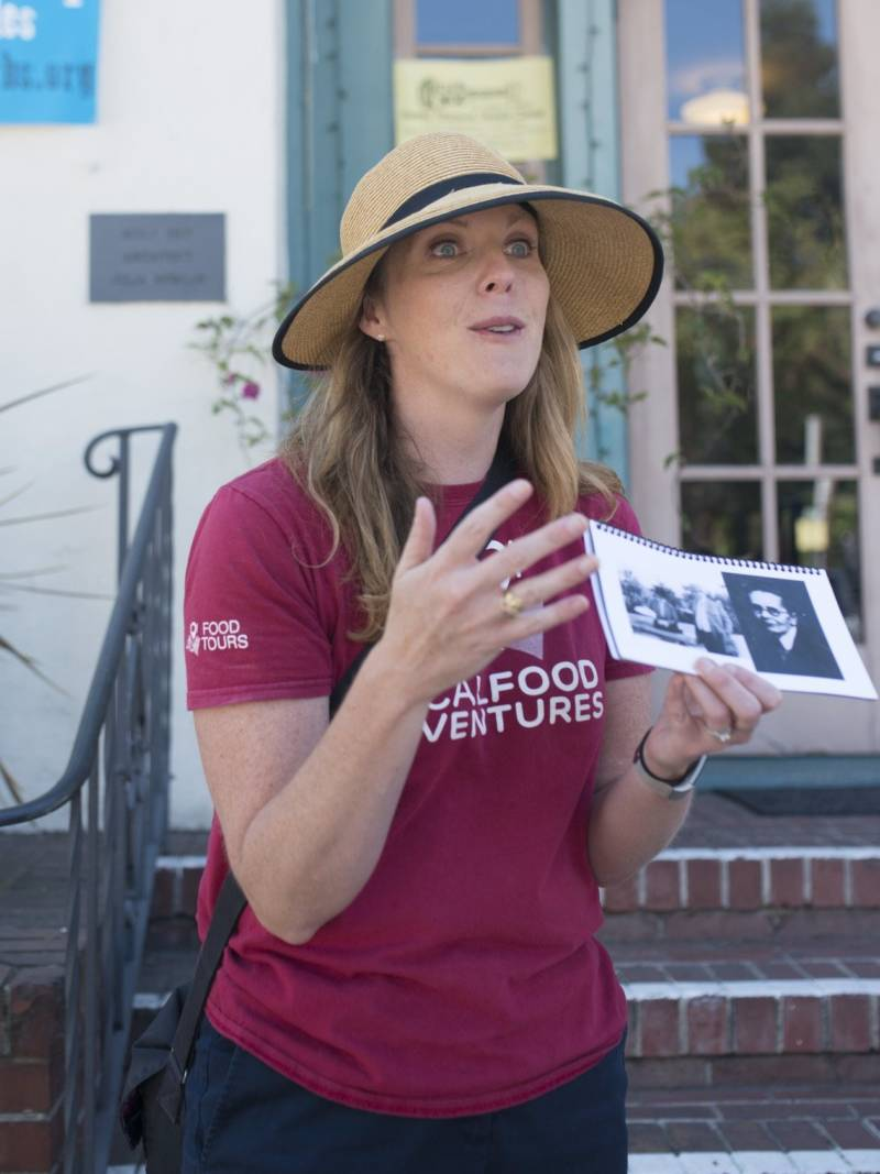 Tour guide Lauren Herpich, of Local Food Adventures, holds up historical photos as she gives an ice cream tour of Oakland's Rockridge neighborhood.