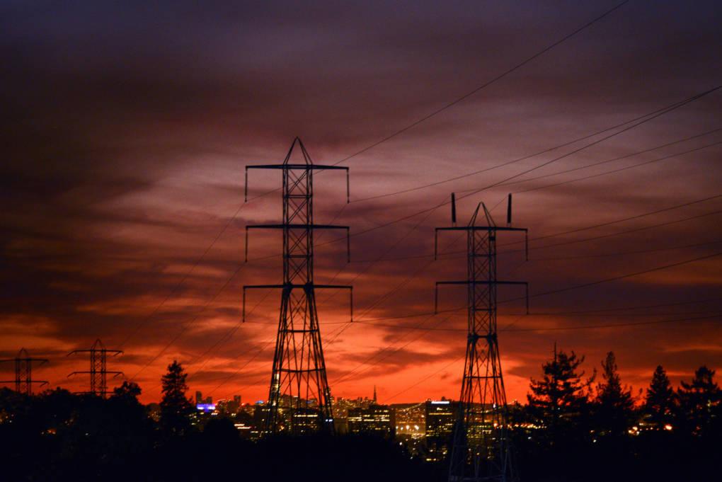 Power lines backlit by a bold orange sunset.