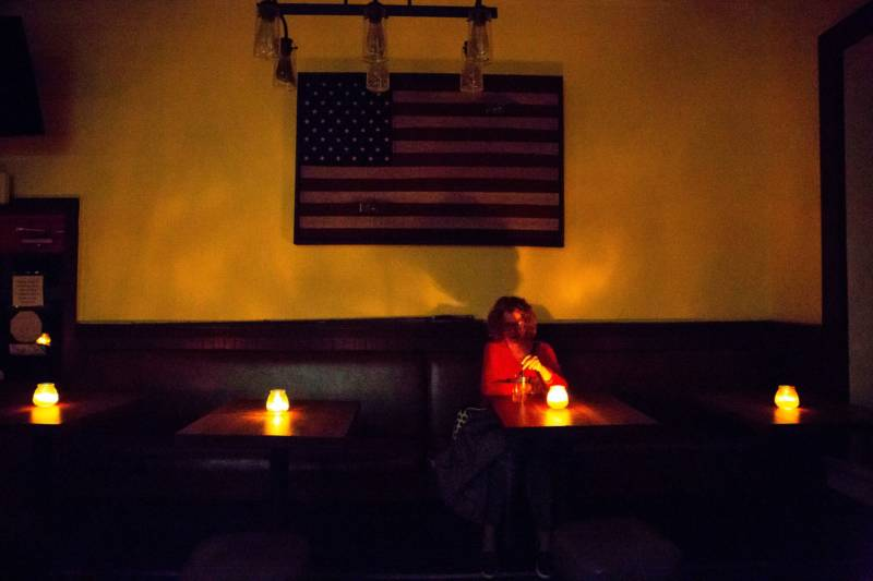 Judy Aquiline, a Sonoma local, sits in the candle-lit restaurant Reel and Brand in Sonoma on Oct. 9, 2019, during a planned power outage by the Pacific Gas & Electric utility company.