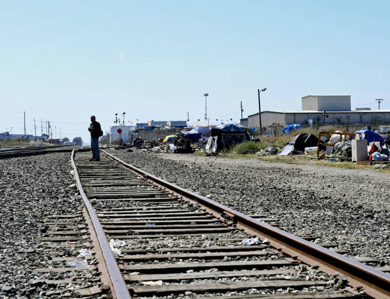 A man walks the railroad tracks along the edge of a homeless encampment where he stays on June 12, 2019.