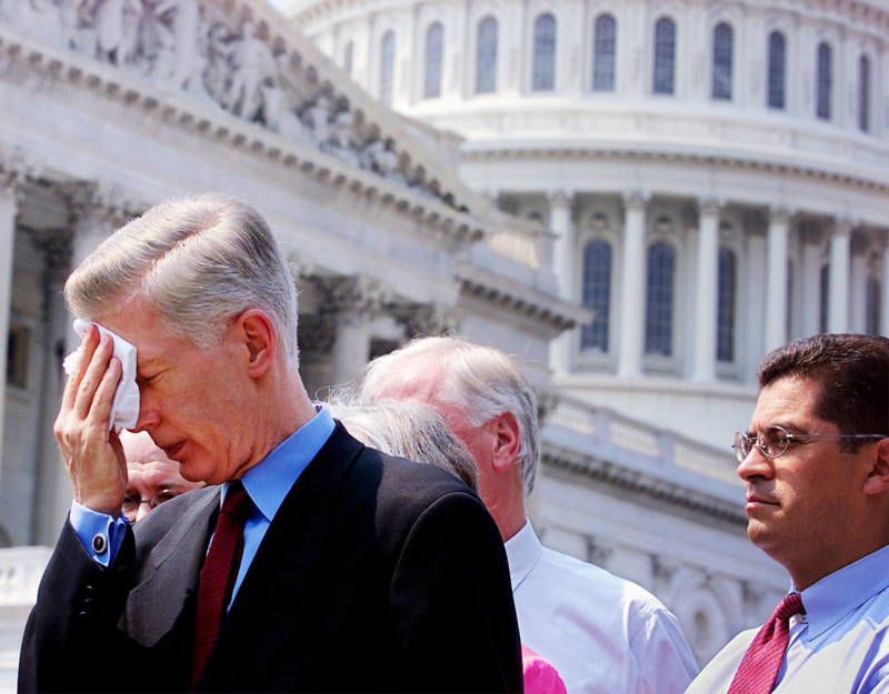 Gov. Gray Davis (L) wipes his brow after delivering a press statement on Capitol Hill, Washington, DC, after testifying in Congress on June 20, 2001 as then-Rep. Xavier Becerra (R), D-CA, listens. Davis blamed a Republican-led energy regulatory agency for not helping during California's energy crisis.