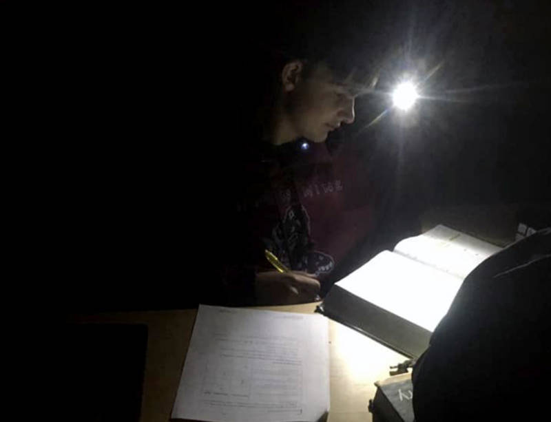 Alecxander Cooper, 13, of Shingle Springs, does homework by headlamp in one of PG&E's power shutoffs in October.