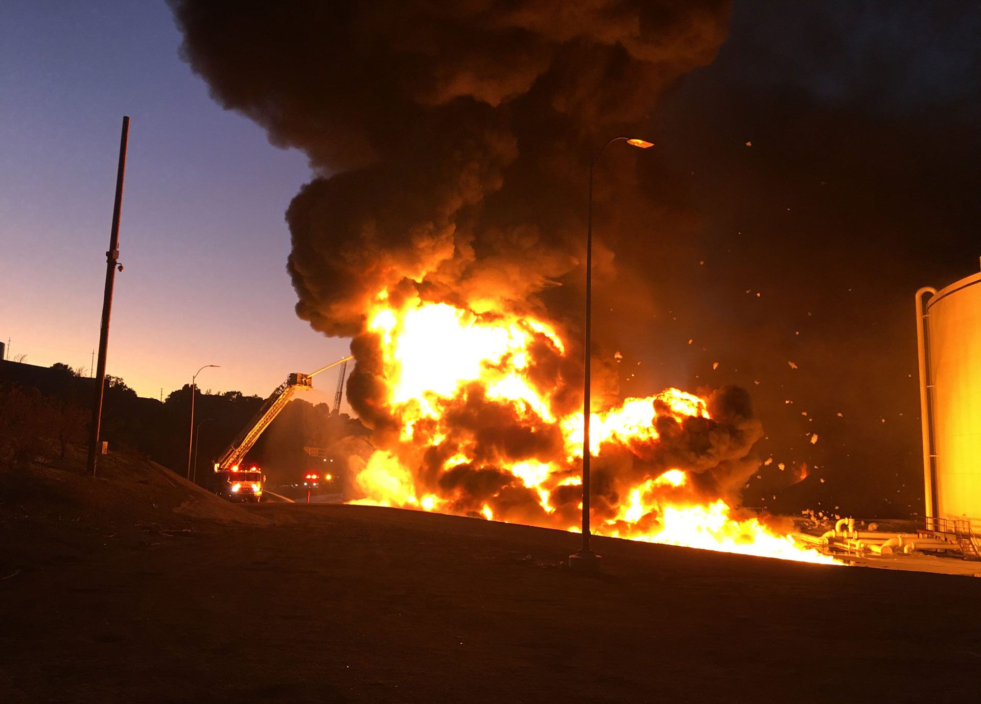Firefighters work to protect adjacent storage tanks after a flare-up at NuStar Energy's facility in Crockett on Tuesday evening.