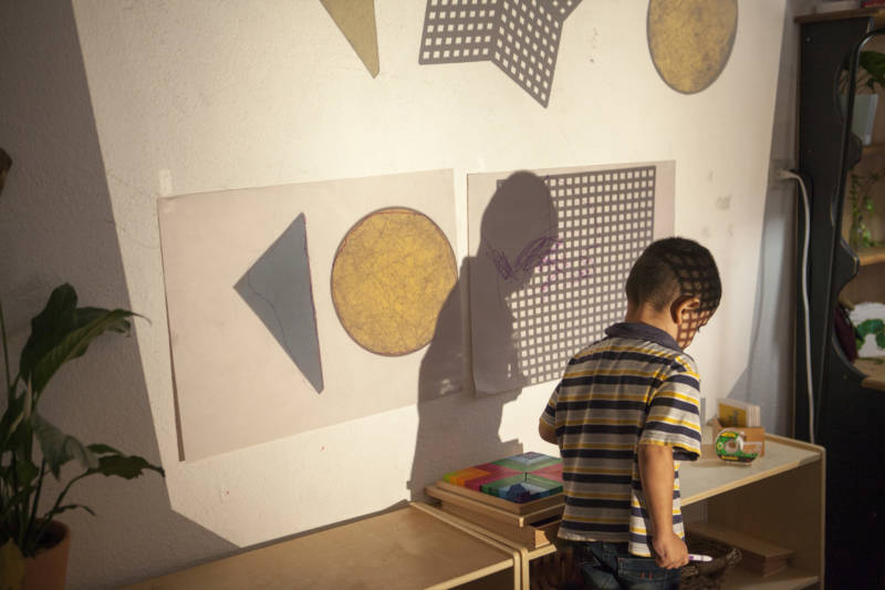 """A child walks through shapes projected on a wall at """"The Nest"""" in Tijuana."""