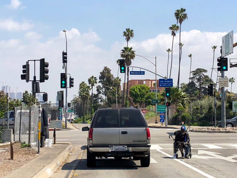 A disabled homeless man begs for change at the Western Avenue exit from the Santa Monica Freeway.