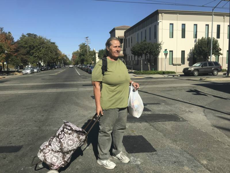 Photo of Sharon Johnston-Corson stands in the middle of the street with a plastic bag on her hand and a rolling bag on the other.