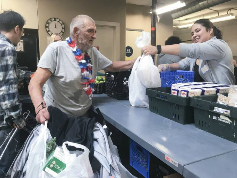 Photo of Richard Valentin standing in line to pick up food from the River City Food Bank. He places the bags of food on his walker.