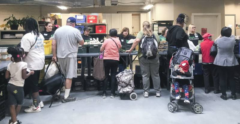 """Photo of people going through an assembly line to pick up groceries. There is a sign above the line that reads """"nutrition."""""""