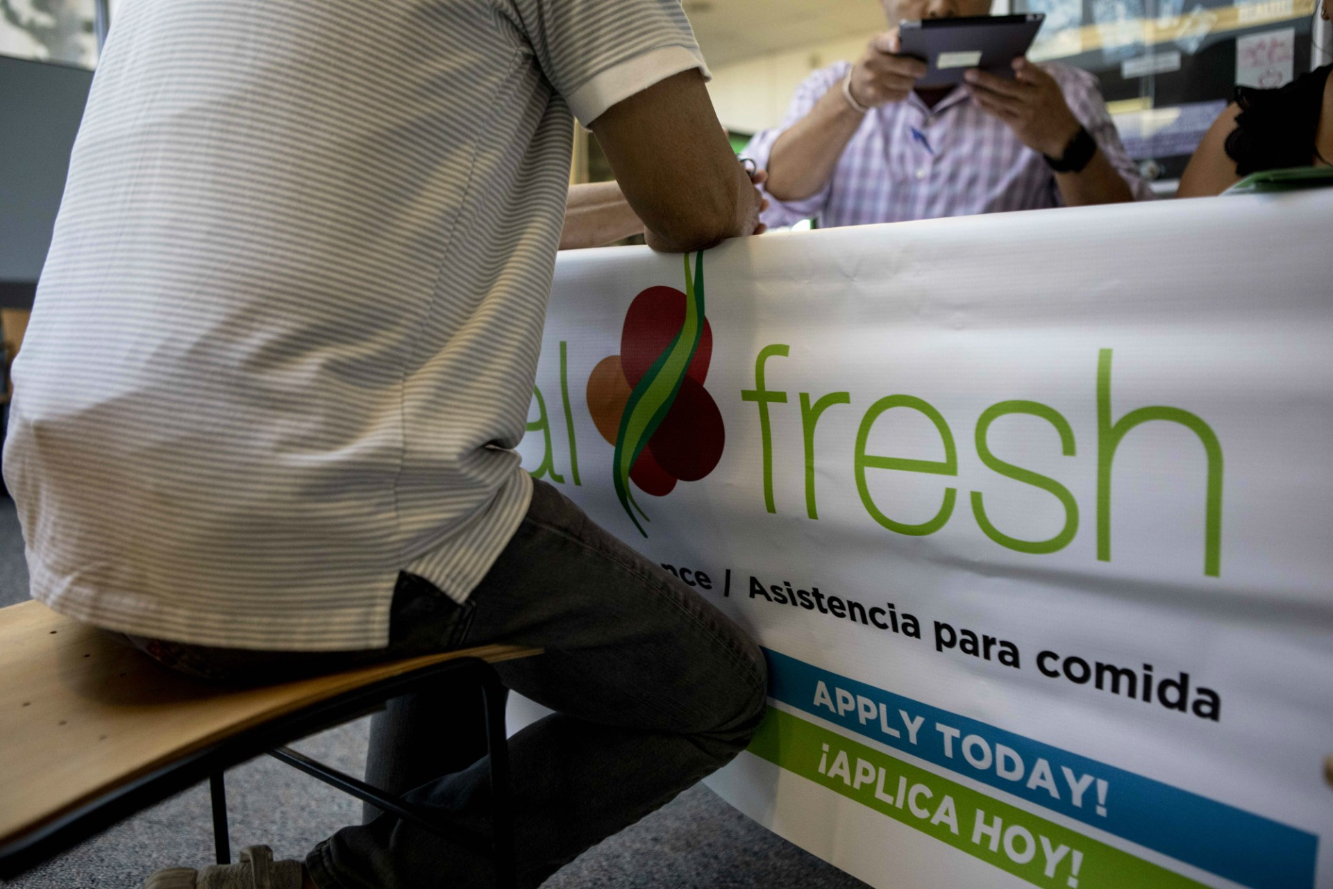 Photo of a man signing a document at a table with an ad that says CalFresh.