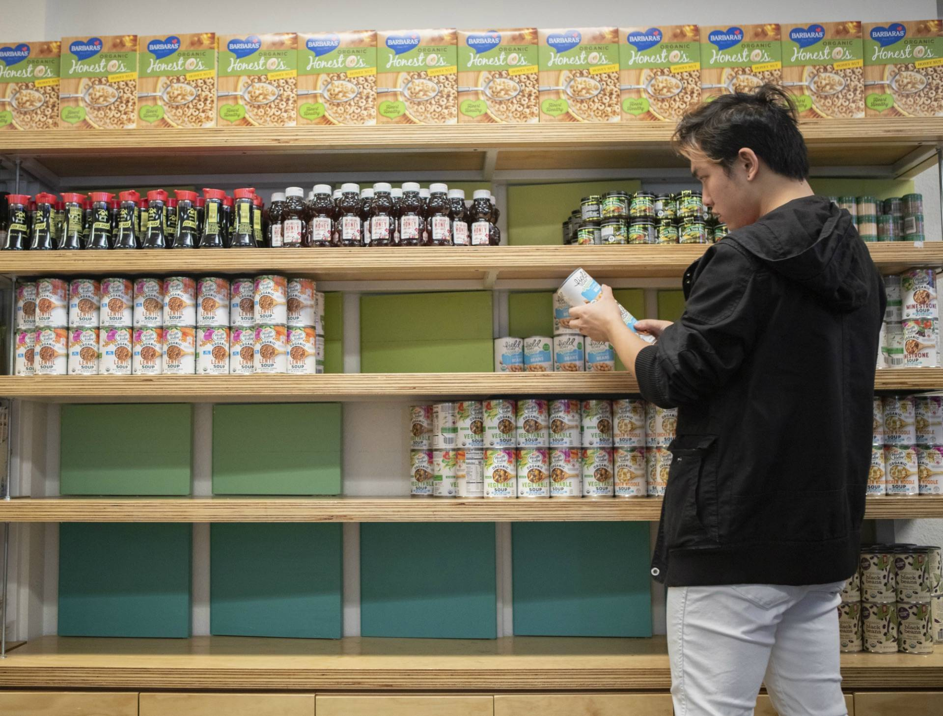 Student volunteer Yongjie He restocks shelves with canned goods at the UC Berkeley campus food pantry.  Anne Wernikoff for CalMatters