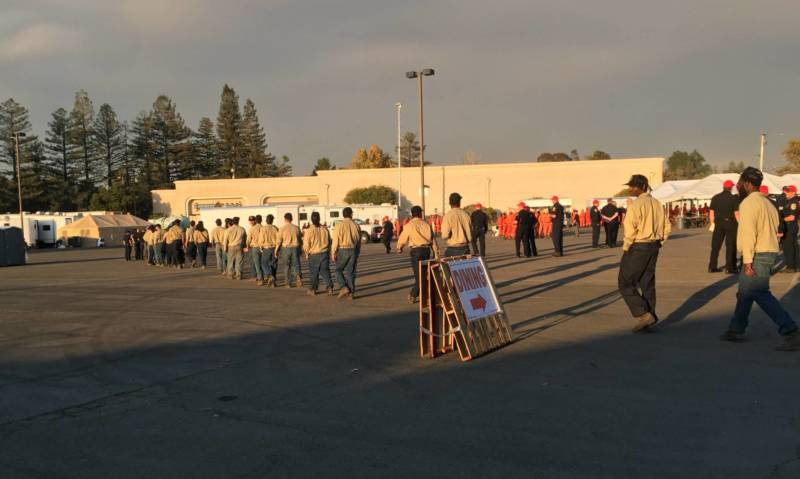 Inmate firefighters file into the Cal Fire command center.