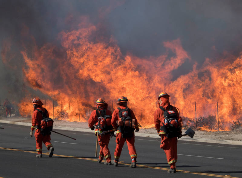 Inmate firefighters prepare to put out flames on the road leading to the Reagan Presidential Library during the Easy Fire in Simi Valley on Oct. 30, 2019.