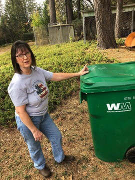 Kathy Lafayette stands next to a garbage receptacle full of mulch from her mother's yard in Grass Valley. The family spent more than $3,000 fire proofing their property this year and still lost their coverage.