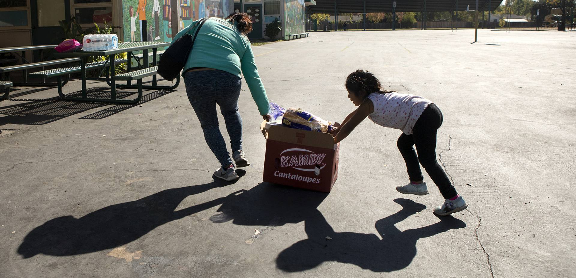 A mother and daughter push a crate of food across the yard at El Verano Elementary School during a food distribution for families affected by October's planned power outages.  Anne Wernikoff for CalMatters