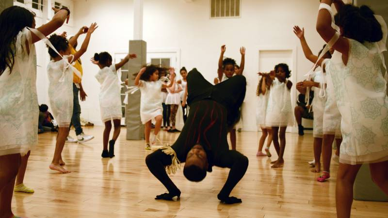 James Davis, who dances Exu, break-dances with a group of snow angels during a rehearsal at Sullivan Community Space in Oakland on Dec. 8, 2019.