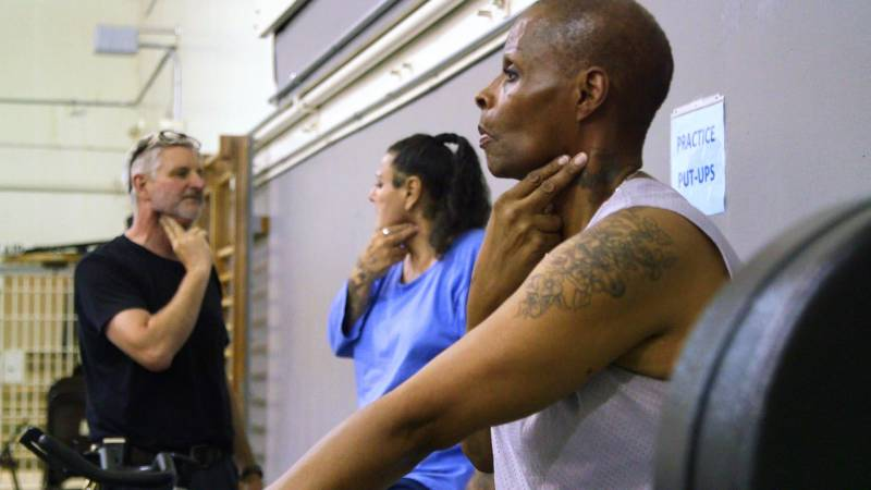 James Star Henderson (right) and Mark Peaches Cate, two transgender woman housed at the California Medical Facility in Vacaville, take their pulse after exercising in the prison gym on June 11, 2019. Pictured left is their coach, Jeremiah Holland.