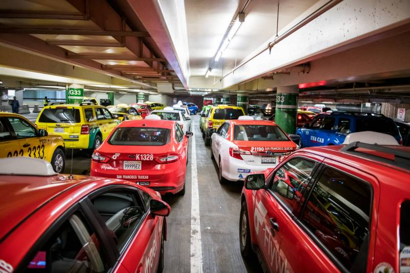 Taxis wait to pick up passengers at San Francisco International Airport on Jan. 30, 2020. With about 500 taxi drivers coming to SFO daily, each driver may get only as few as three rides a day.