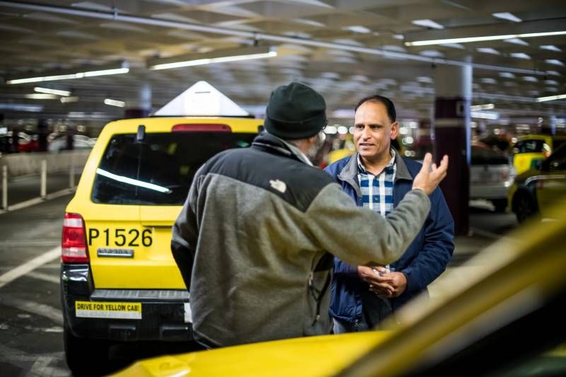 Taxi drivers Ali Asghar (L) and Namdev Sharma (R) talk while they wait for a fare at San Francisco International Airport on Jan. 30, 2020.