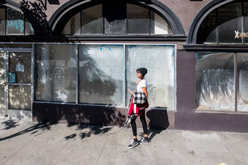 A woman walks past a series of empty Upper Haight storefronts in San Francisco on Tuesday, Feb. 25, 2020. The store on the left was previously occupied by Kids Only, which closed in 2016. The store on the right housed X Generation, which closed in 2017.