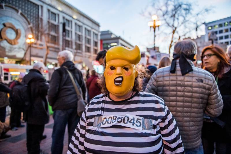 Christine Diehl wears a Trump mask at a protest against the Senate's acquittal of President Trump on two impeachment charges.