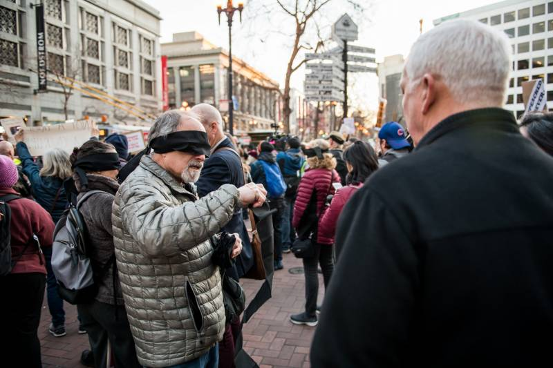 Michael Kesselman hands out blindfolds at the Reject the Coverup protest at Powell and Market Streets in San Francisco on Feb. 5, 2020. He said that justice should be blind but not blinded.