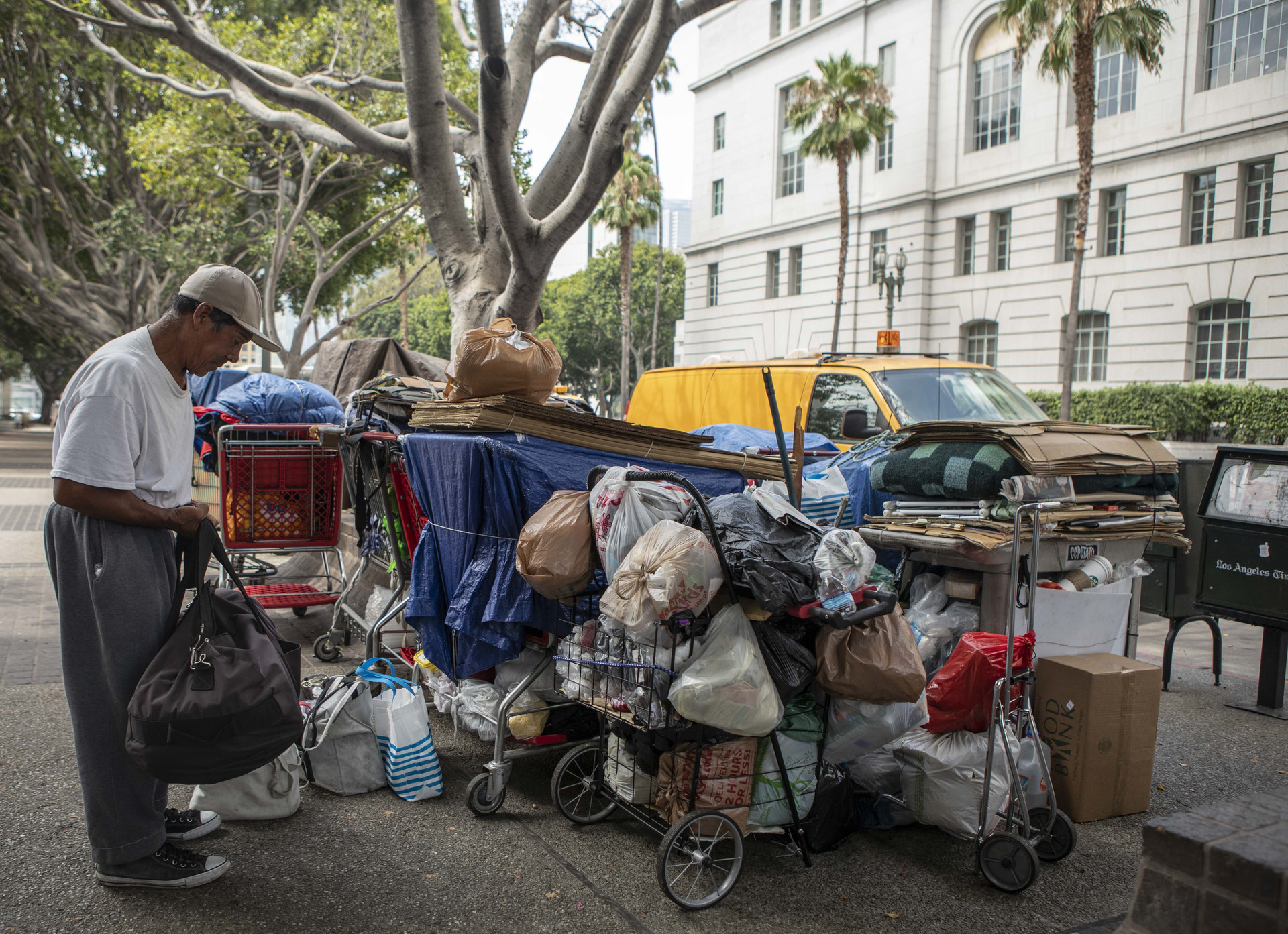 Esteban Gonzalez keeps watch over a dozen shopping carts full of personal items belonging to a group of homeless individuals across the street from Los Angeles City Hall on August 7, 2019. According to Gonzalez, someone must stay with the shopping carts at all times to avoid having their items taken away by authorities so he and the other participants take turns throughout the day never leaving the carts unattended.