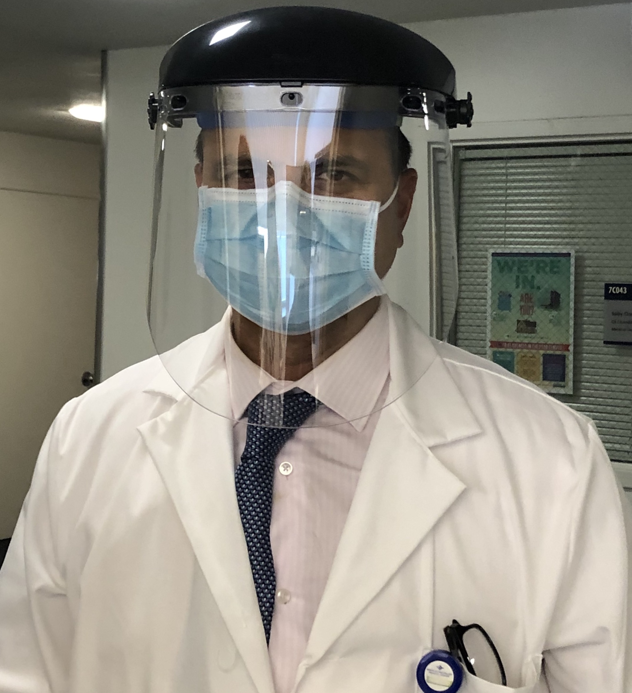 Dr. Sanjay Kurani, hospital medical director at the Santa Clara Valley Medical Center, models a plastic face shield worn over a surgical mask.