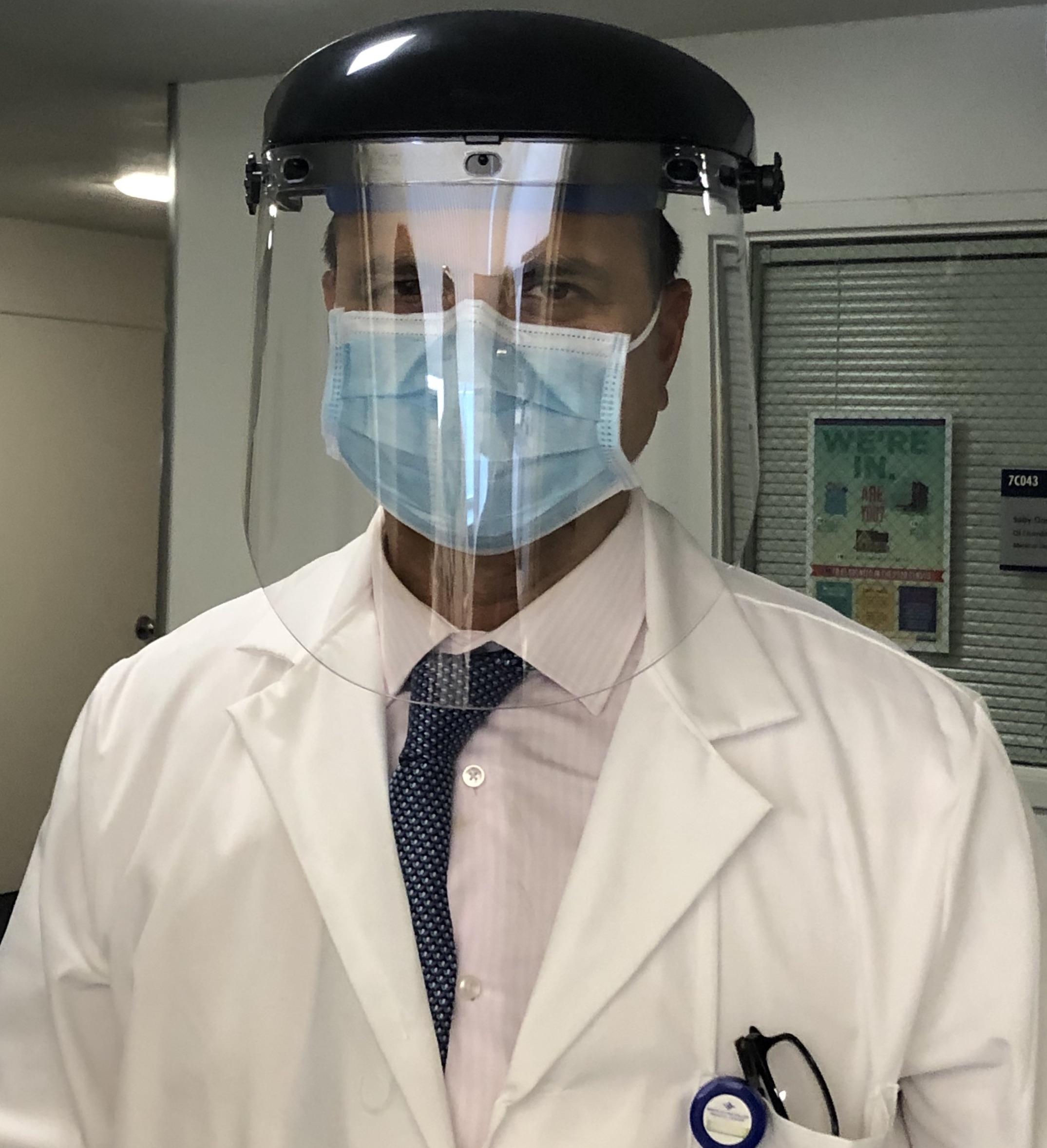 Dr. Sanjay Kurani, hospital medical director at the Santa Clara Valley Medical Center, models a plastic face shield worn over a surgical mask.