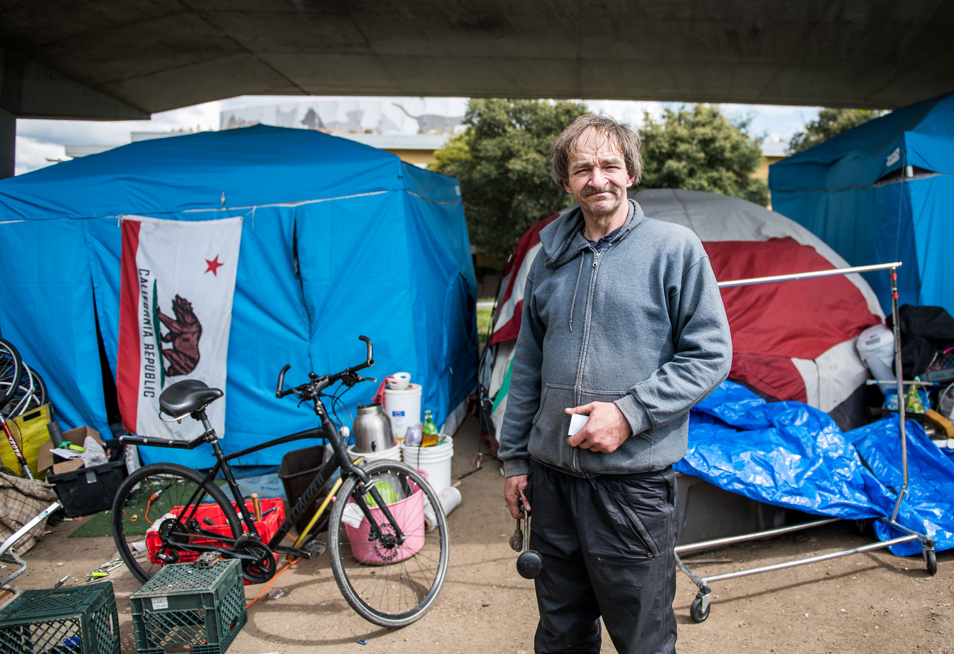 "Kevin Coddington, 52, at the tent encampment where he lives under a freeway overpass in Berkeley on Mar. 19, 2020. When asked about outreach to his community in response to the coronavirus crisis, he said, ""It's very scary. They haven't given us anything."" He said that private donations were all that they had received, which helps them to supply their own portable restrooms, but that they could use running water as well as masks, gloves and sanitizer."