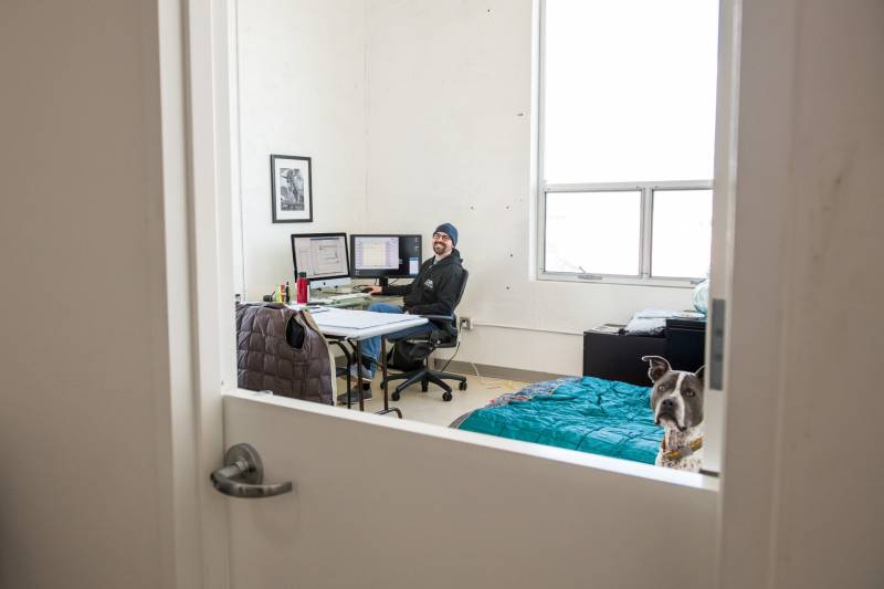 Katie Wojnoonski and her husband Andy (pictured) are sheltering in place in the offices of the Dog Social Club in Oakland.