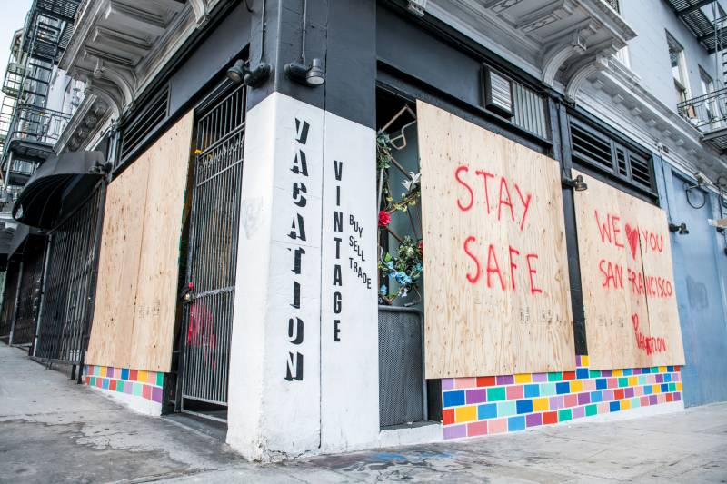 The owners of the vintage clothing store Vacation in the Tenderloin put boards over their windows as they closed their brick and mortar store after shelter-in-place orders were issued on Tuesday, Mar. 17, 2020. They are hopeful that online sales will continue, but worry for the future.