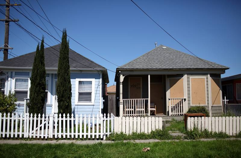Two houses, side by side, one with boarded-up windows.