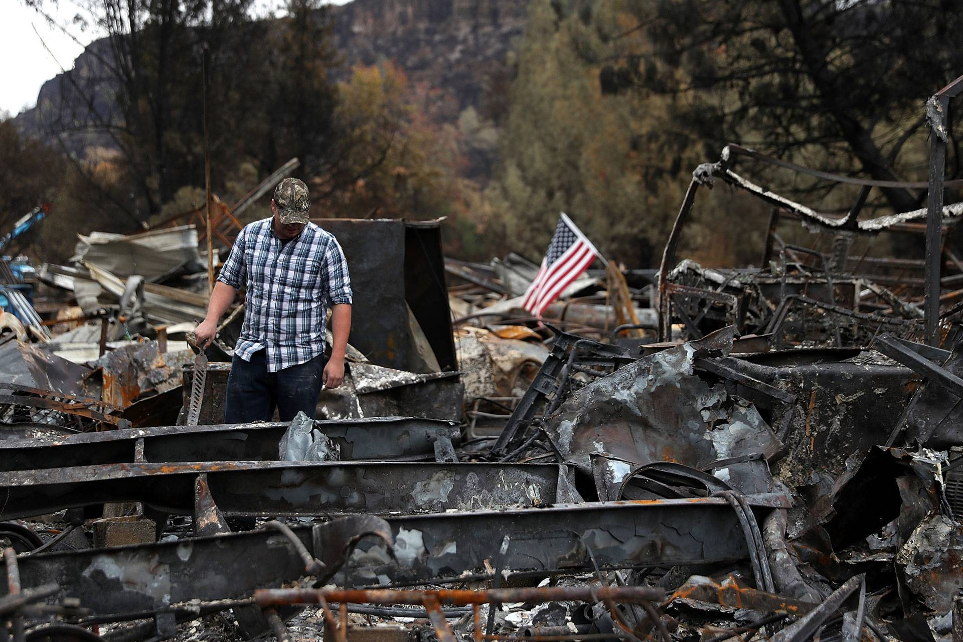 A man looks over his burned home, destroyed by the Camp Fire in Nov. 2018 in Paradise. The deadline for 70,000 survivors of numerous fires to vote on a multi-billion-dollar settlement deal with PG&E was May 15. Justin Sullivan/KQED