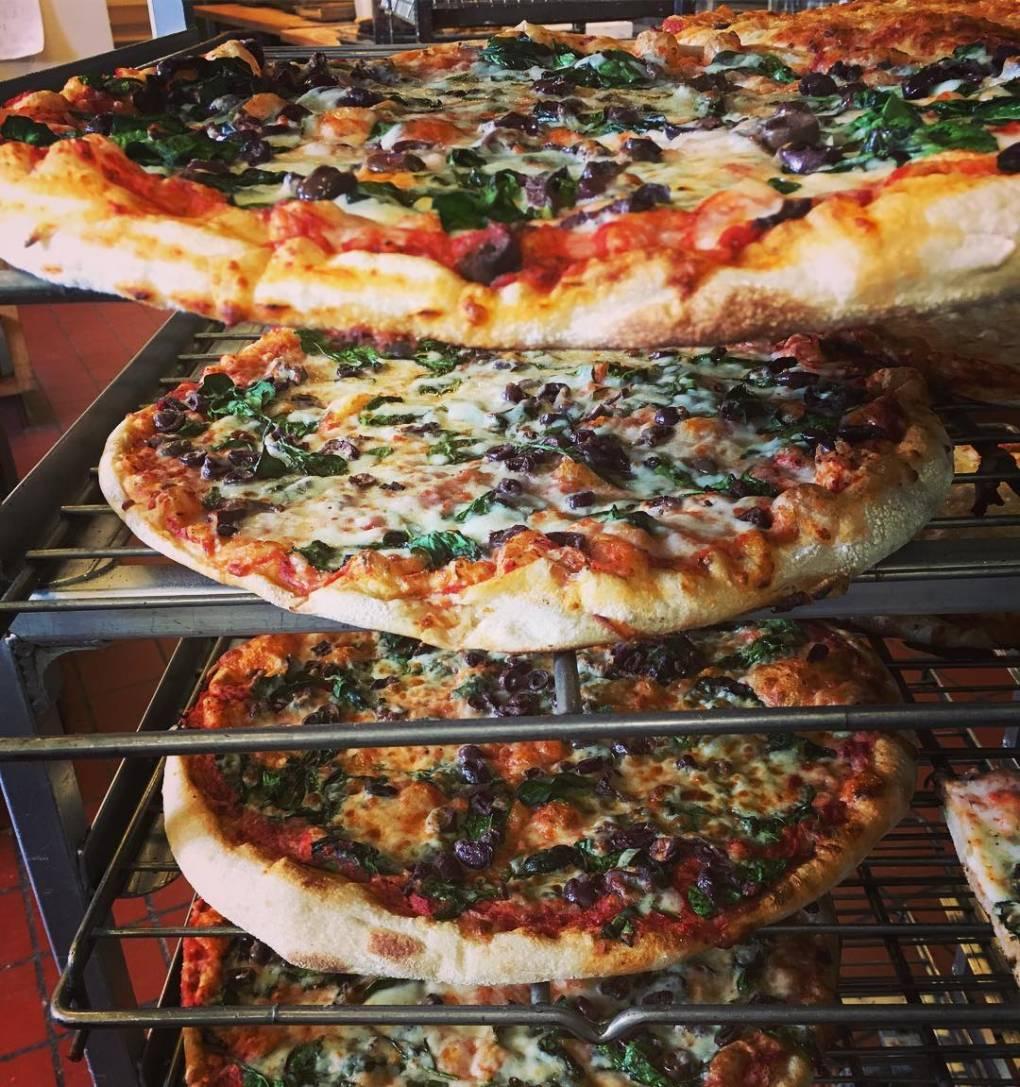 Arizmendi Bakery pizzas cool on a rack.