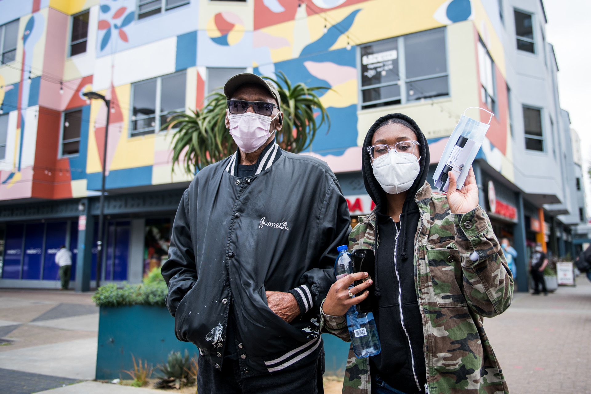 Chelsea Riley (right) and her father James Riley line up to receive free hand sanitizer and a face mask in the Fillmore on April 17, 2020.