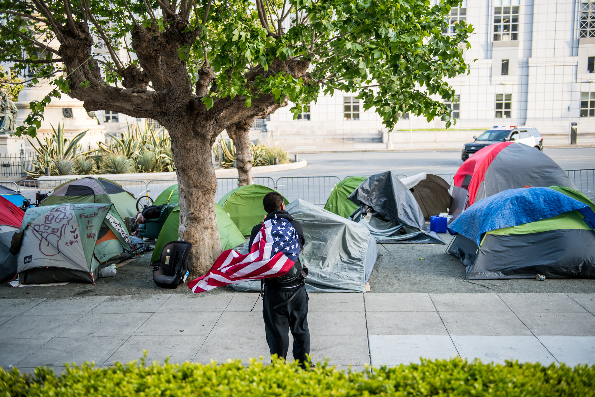 Tents line a gravel sidewalk off Fulton Street near City Hall on May 5, 2020. On Wednesday, city staffers started drawing out socially distant spaces with chalk on the street for the tents to stay.