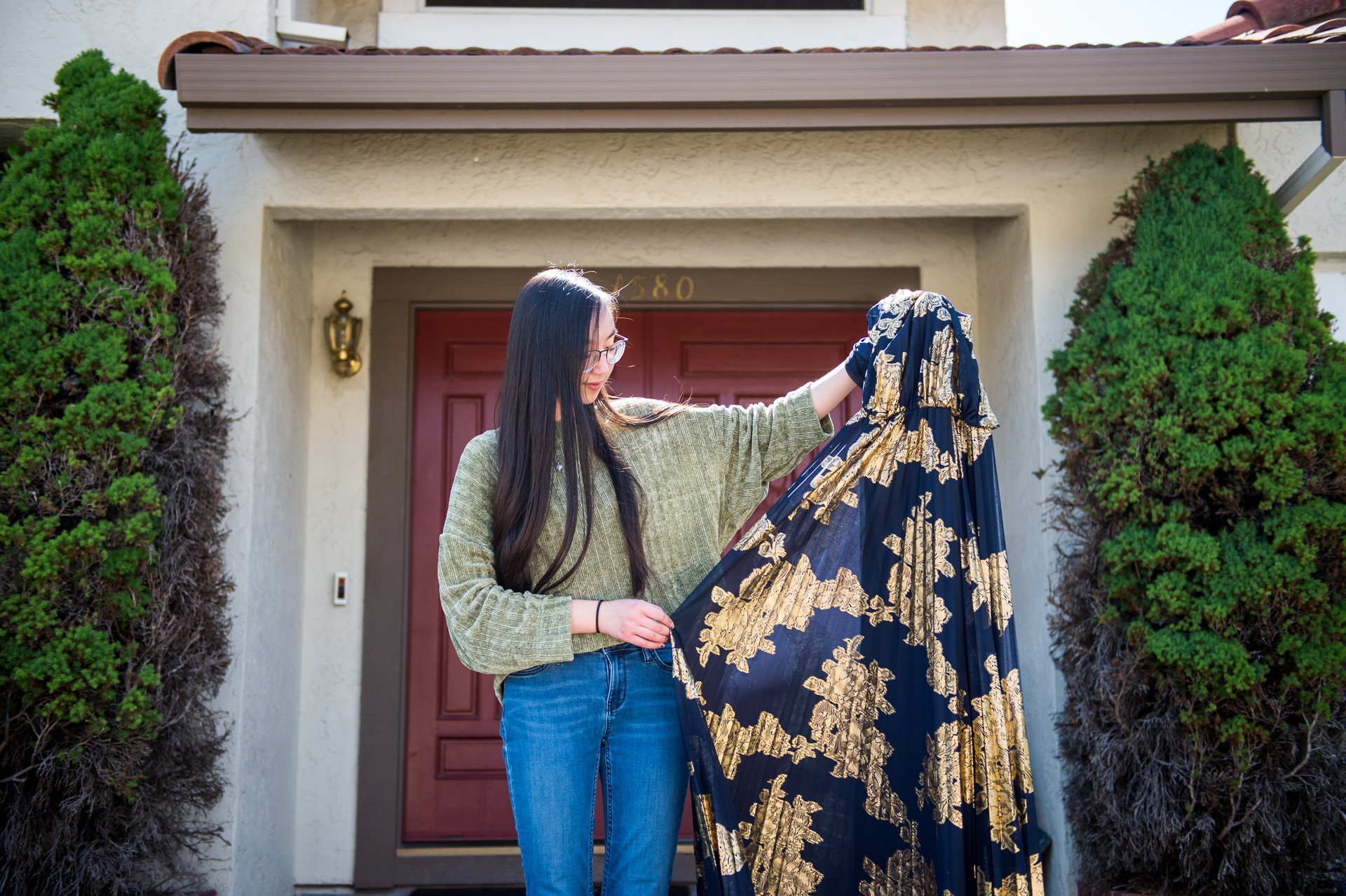 High school senior Taila Lee holds her prom dress at her home in San Carlos on April 4, 2020.