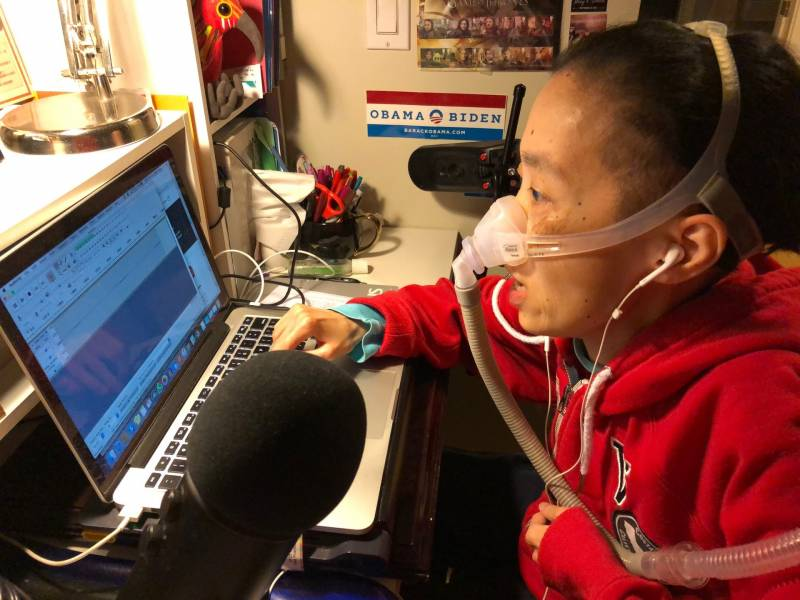 Disability rights activist Alice Wong podcasting at her desk at home.