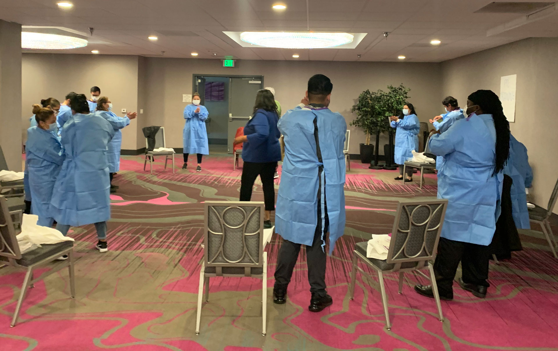 Alameda County public health staff take part in a training on how to use personal protective equipment while working with guests at the Radisson Hotel in Oakland in late March.