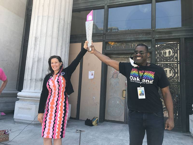 Oakland mayor Libby Schaaf and Joe Hawkins, founder of Oakland Pride and CEO of the Oakland LGBTQ Community Center, hold up the Pink Torch as they kick off the procession outside Oakland City Hall.