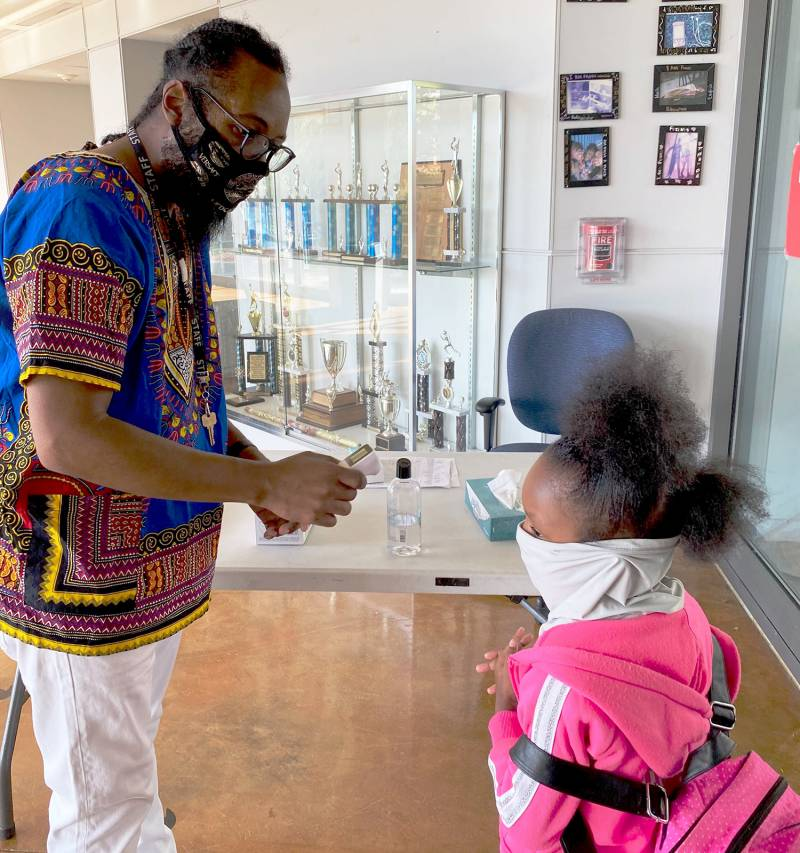 Administrative assistant Julius Holtzclaw checks a kindergartner's temperature when she arrives at school.