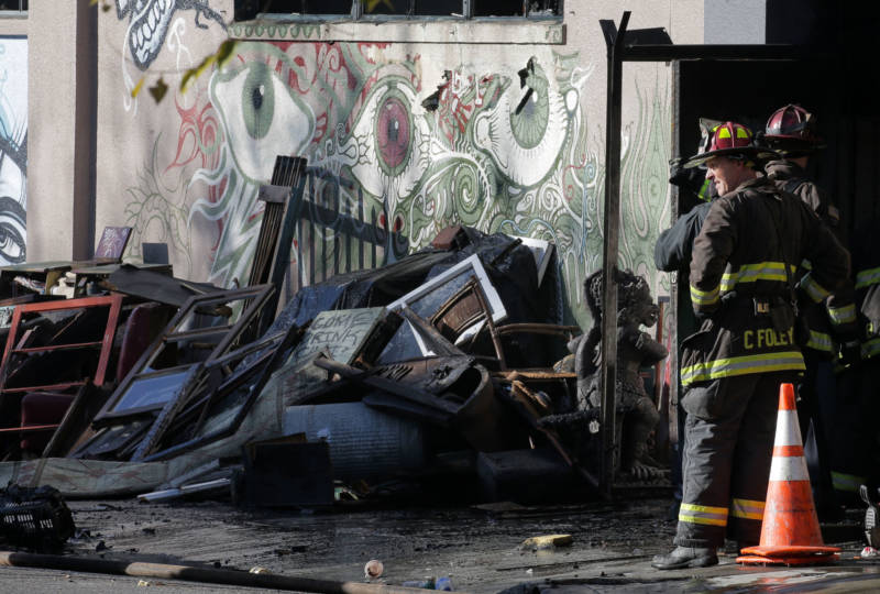 Firefighters work outside the Ghost Ship warehouse on the morning of Dec. 3, 2016 in Oakland, the day after a fire there claimed the lives of 36 people.