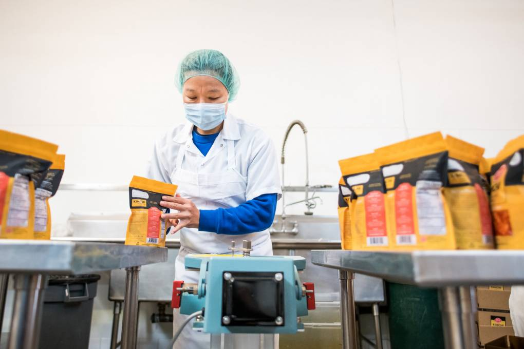 Hyunjoo Albrecht works in her Bayview kitchen to package kimchi on August 6, 2020. Beth LaBerge/KQED